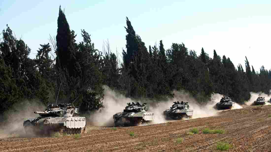 A convoy of Israeli tanks roll near Israel's border with the Gaza Strip on Friday. There's a sense of repetition to the violence in the region, as Hamas fires rockets at Israel and Israel responds with bombs and the threat of a ground invasion.