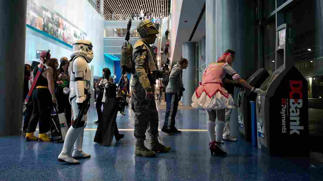 Anna Swope, dressed as a stormtrooper from Star Wars, and her husband Stephen Goss, dressed as the films' Boba Fett, wait to use an ATM while attending the Fan Expo convention in Vancouver, B.C.