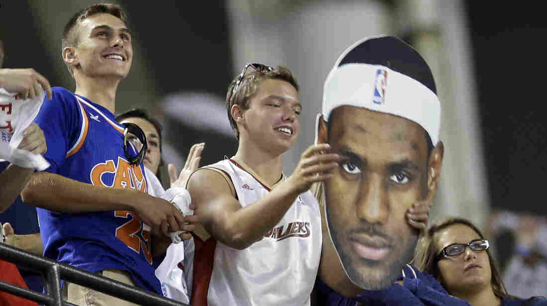 A Cleveland Cavaliers fan holds up a LeBron James poster at a New York Yankees game Thursday. One day later, the fan's wish was granted: James will return to the Cavs for this year's new season.
