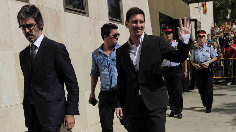 Barcelona football star Lionel Messi (right) leaves a courthouse in Gava, Spain, in September 2013, after a hearing on tax evasion charges. Messi and his father paid $6.5 million to try to settle the case, but his father may still go on trial.