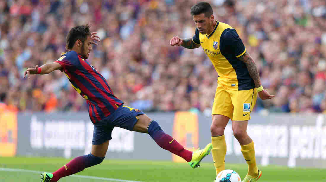 Allegations surrounding the signing of Neymar da Silva Santos Júnior of FC Barcelona (shown here, left, tackling Jose Sosa of Club Atletico de Madrid on May 17 in Barcelona) are at the heart of tax fraud charges against the storied soccer club.
