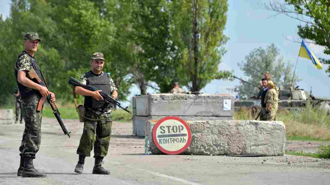 Ukrainian soldiers man a checkpoint about 30 miles from Donetsk on Thursday. A government official said Friday that a rocket attack had killed as many as 30 troops.