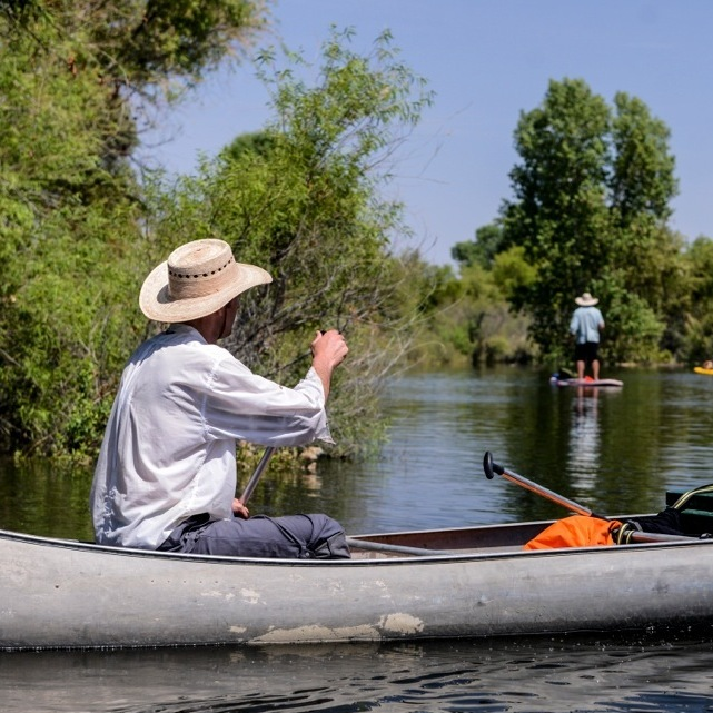 "Rowan Jacobsen, in the canoe, and Pete McBride and Sam Walton, on stand-up paddleboards, travel through the upper limitrophe of the delta reach (the section marking the U.S.-Mexico border). Before the dam release, Jacobsen described this parched riverbed as a scene of ""Mad Max misery."" The temporary flow of water helped bolster native habitats that survive here."