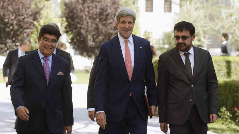 Secretary of State John Kerry walks across the presidential palace grounds with Afghan Foreign Ministry officials on Saturday. Kerry helped broker a deal for a full recount of presidential election results.
