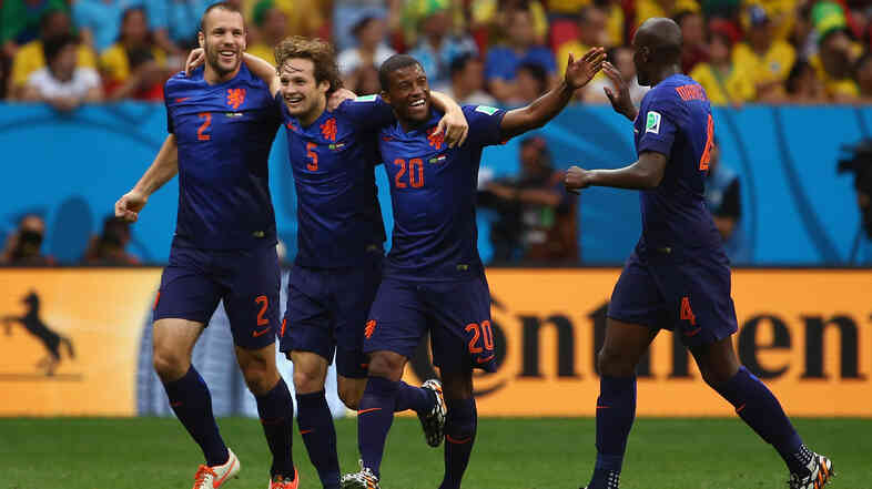 Daley Blind of the Netherlands (5) celebrates scoring his team's second goal with Ron Vlaar (2), Georginio Wijnaldum (20) and Bruno Martins Indi (right) during the 2014 FIFA World Cup Bra