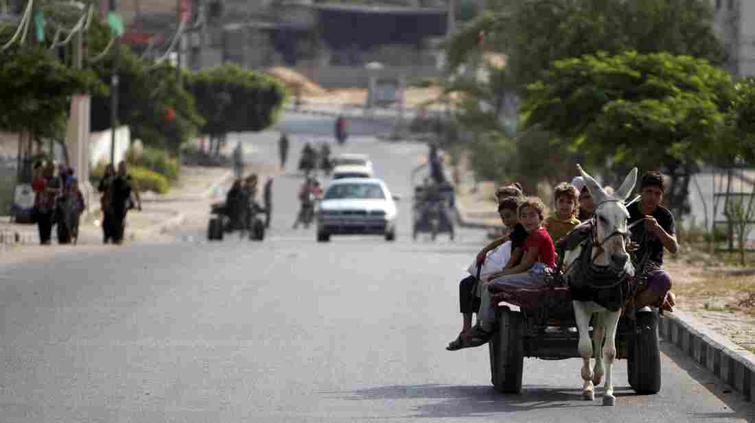Palestinian families travel to a United Nations school to seek shelter after evacuating their homes near the Israel-Gaza border Sunday. Israel has been warning residents to leave.