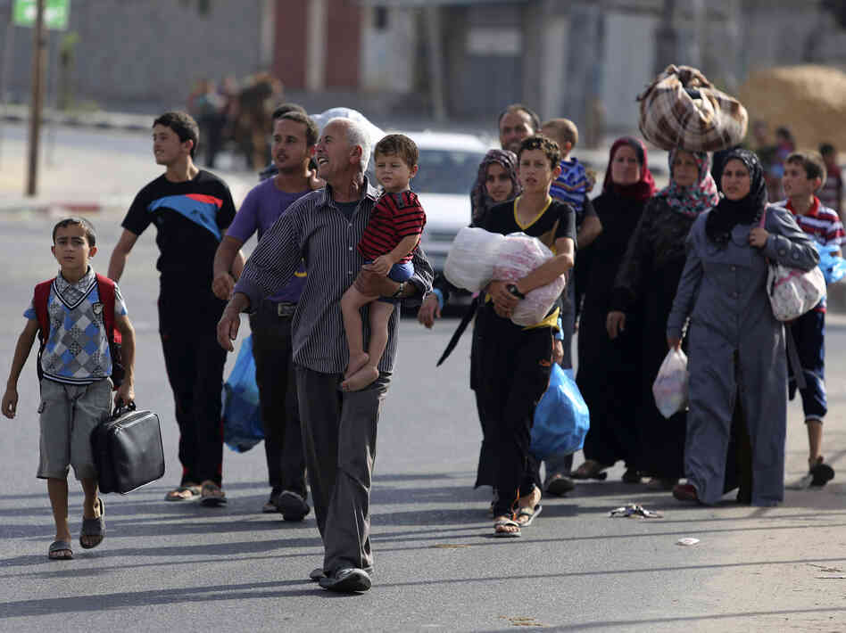Palestinians flee their homes to take shelter at the United Nations school in Gaza City, on Sunday. Israel has dropped leaflets warning residents to leave ahead of stepped up fighting.
