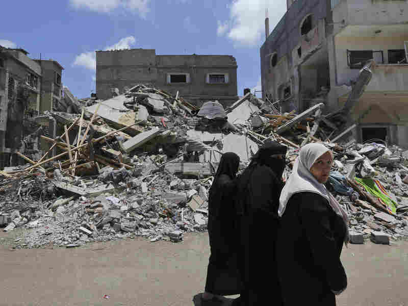Palestinians walk by the rubble of a house destroyed by an overnight Israeli missile strike on Monday.