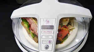 A model of General Electric's automatic calorie counter, fitted over a plate of food.
