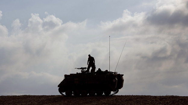 An Israeli soldier stands on a military vehicle near Gaza early Tuesday, when a cease-fire was meant to take effect. The deal hasn't been embraced by all of Hamas. (AP)