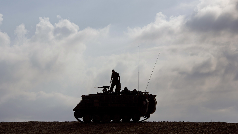 An Israeli soldier stands on a military vehicle near Gaza early Tuesday, when a cease-fire was meant to take effect. The deal hasn't been embraced by all of Hamas.