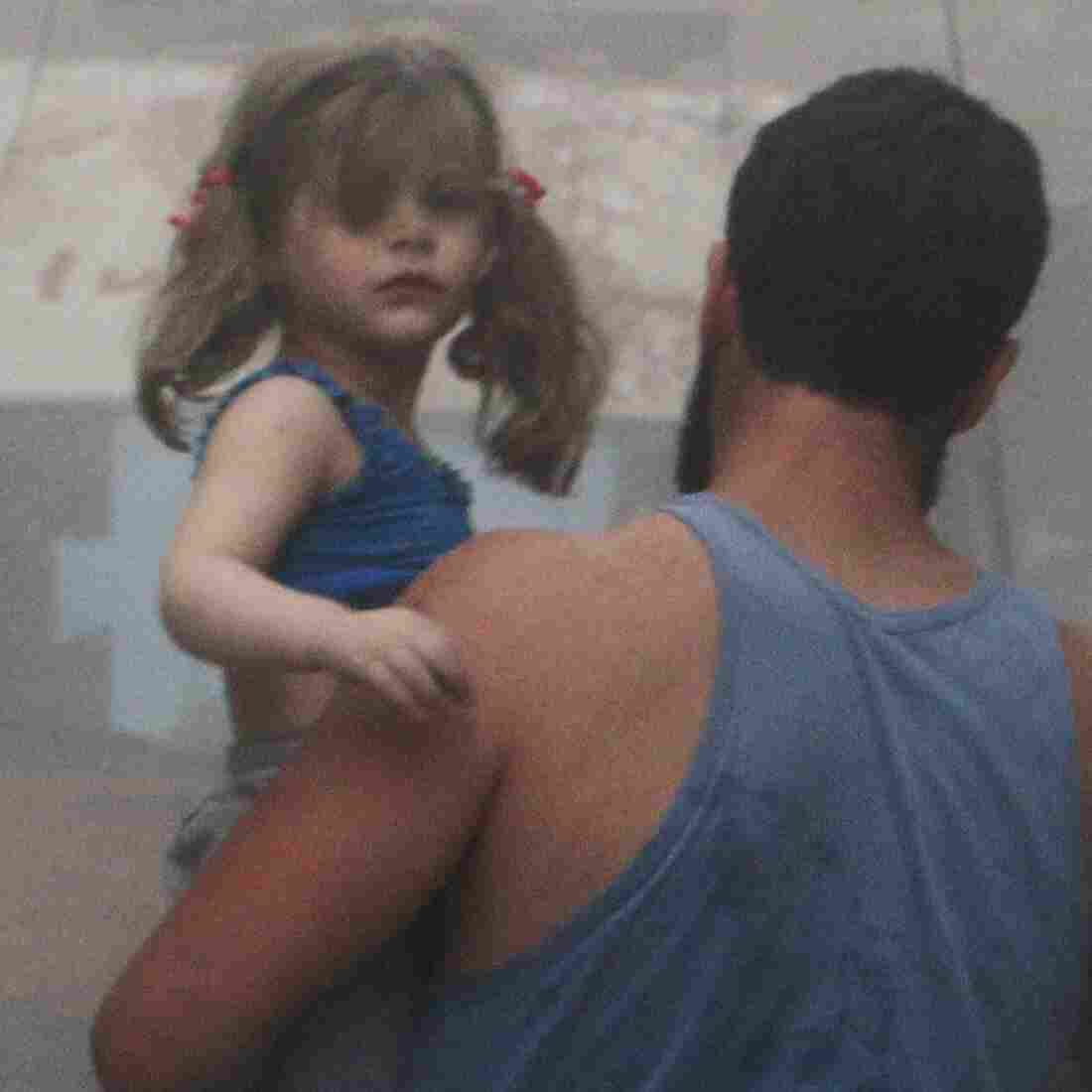 A Syrian man carries a girl on a street covered with dust following a government airstrike in Aleppo on Tuesday. Rebels took the eastern half of the city in 2012 but are now in danger of being forced out by President Bashar Assad's troops.