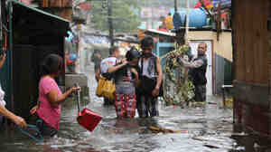 Residents wade through floods as they go back to their home while Typhoon Rammasun batters suburban Quezon city, north of Manila, on Wednesday