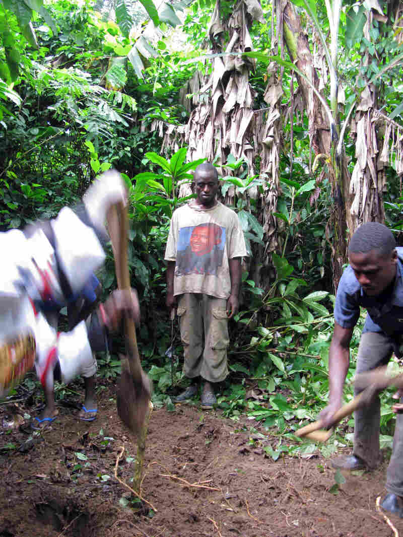 Relatives of Musa James dig a grave for her in the nearby jungle after neighbors objected to her being buried behind her house.