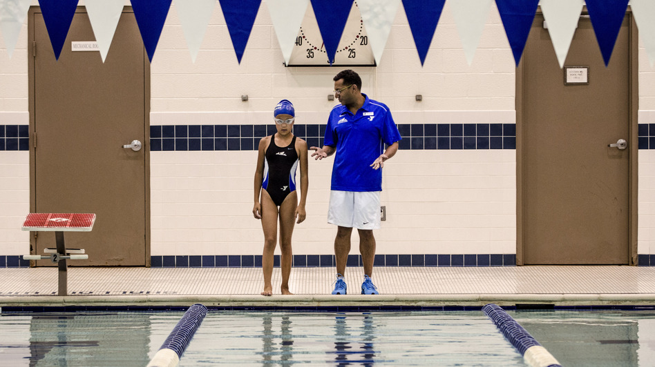 Peri Schiavone, 13, gets some quick notes from her swim coach, Raj Verma, before hopping back into the pool at the Fairfax County YMCA in Reston, Va. (Sarah Tilotta/NPR)