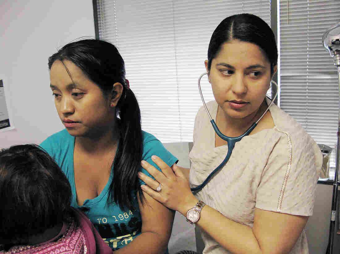 Dr. Charu Sawhney examines patient Mang Caan. Sawhney supports the Affordable Care Act, but has been frustrated by how difficult it is to find specialists who accept some of the plans her patients bought.