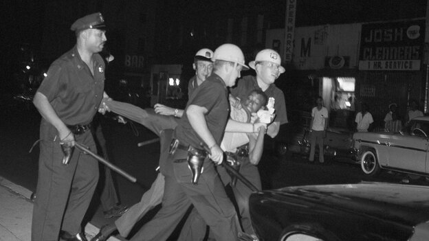 Helmeted New York City police carry away a rioter at West 130th Street and Seventh Avenue in Harlem on July 19, 1964.