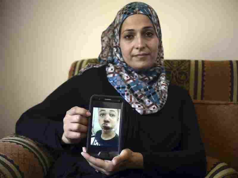 Suha Abu Khdeir, mother of 15-year-old Tariq Abu Khdeir, earlier this month shows a photo of her son after he was allegedly beaten by Israeli police.