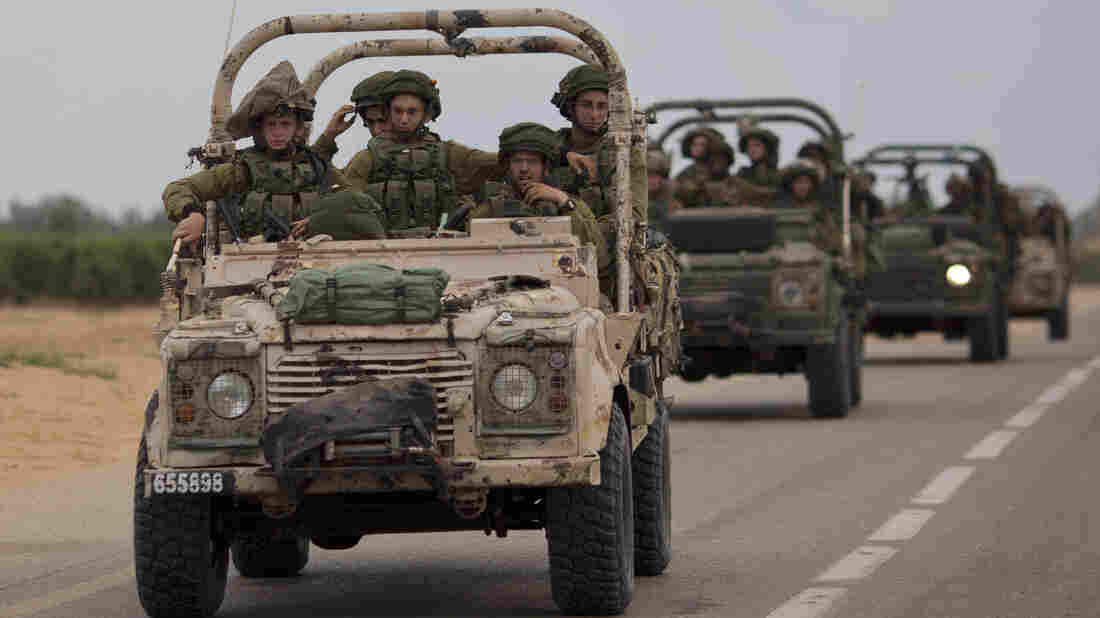 Israeli soldiers ride on military vehicles near the Israel-Gaza border on Thursday