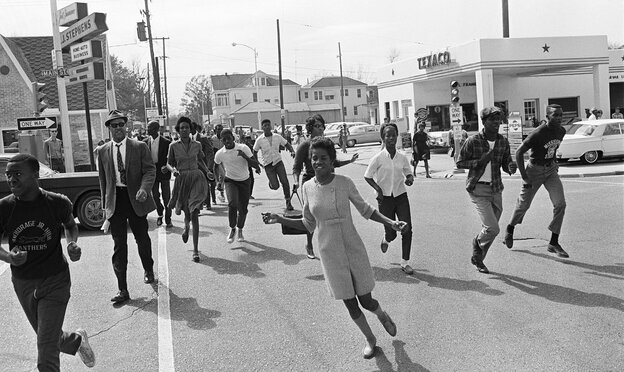 Black demonstrators run down a Natchez, Miss., street in 1967 after a report that several white youths with a gun were near. The town's civil rights past informs author Greg Iles' crime fiction.