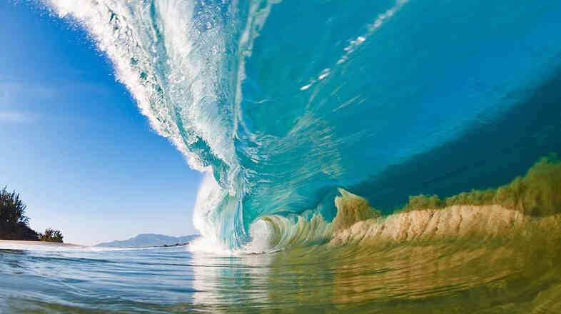 A large wave on the North Shore of Oahu, Hawaii, sucks sand off of the seafloor and into the wave itself. This photo is the cover image of Clark Little's latest coffee table book, Shorebreak.
