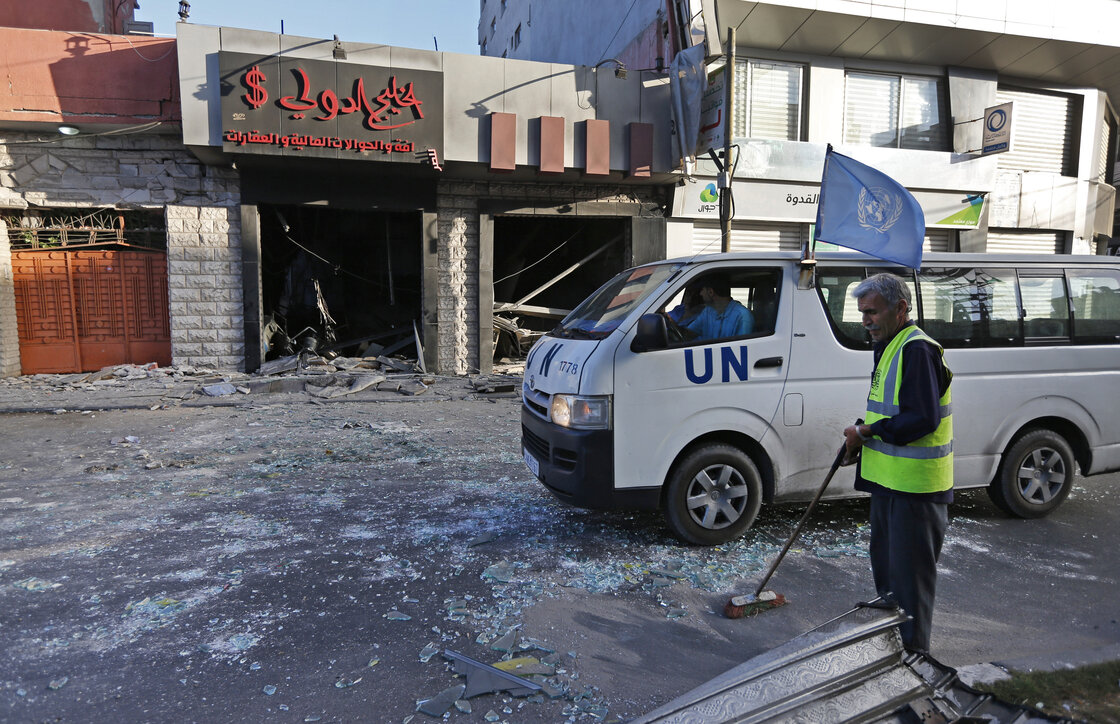 A Palestinian municipality worker sweeps the street as a United Nations vehicle drives past a damaged money exchange post. Israel and Hamas took a break from fighting Thursday for humanitarian reasons.