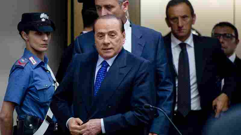 Former Italian Premier Silvio Berlusconi (center) arrives for a court hearing in Naples in June, where he was appearing as a witness in the trial of an associate. Berlusconi's conviction on sex with a minor and abuse of power was overturned by a court in Milan on Friday.