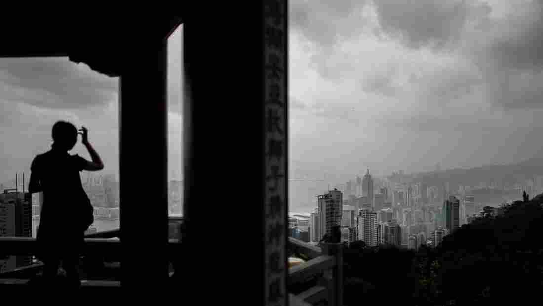 A woman watches thunderstorms gather over Hong Kong's skyline Thursday as Typhoon Rammasun approached.