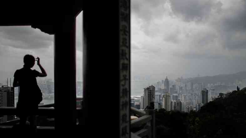 A woman watches thunderstorms gather over Hong Kong's skyline Thursday as Typhoon Rammasun approached.