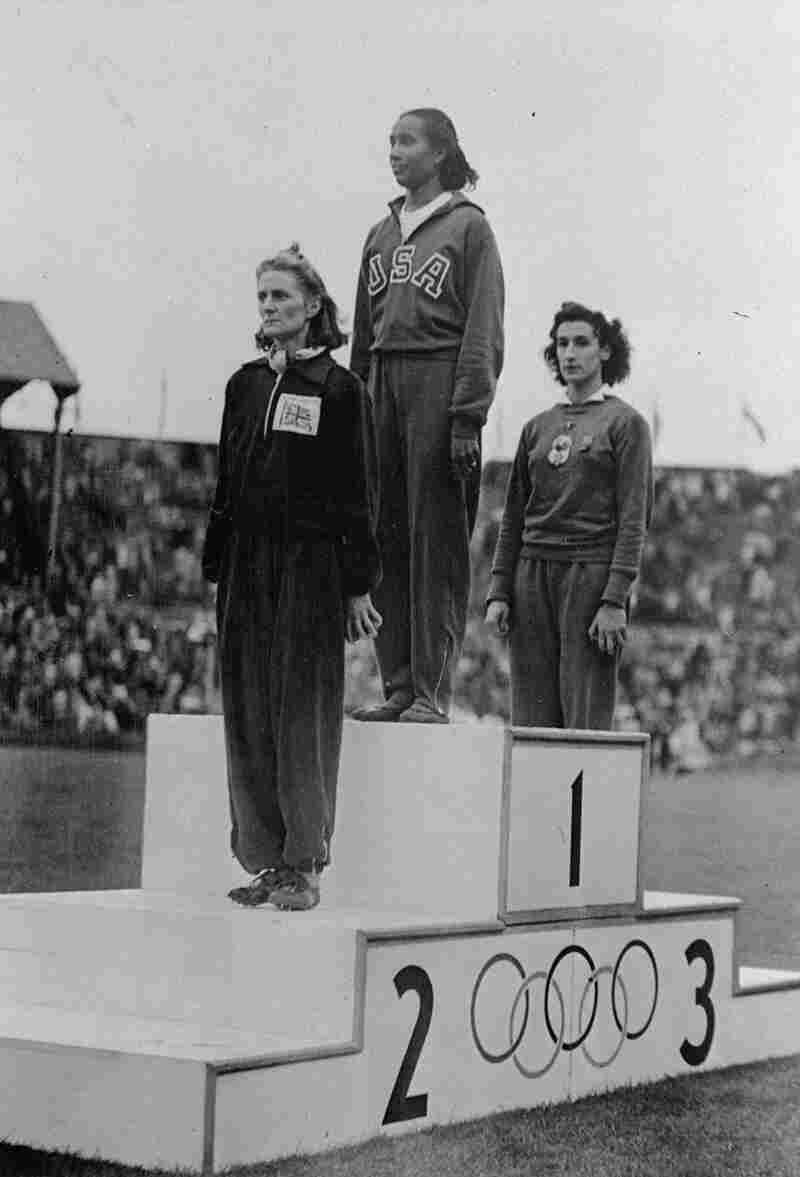 Alice Coachman stands on the winner's section of the Olympic podium at Wembley Stadium in 1948.