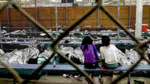 Two young girls, part of the wave of unaccompanied children who've illegally entered the U.S., watch a soccer match at the Customs and Border Protection Nogales Placement Center in Arizona.