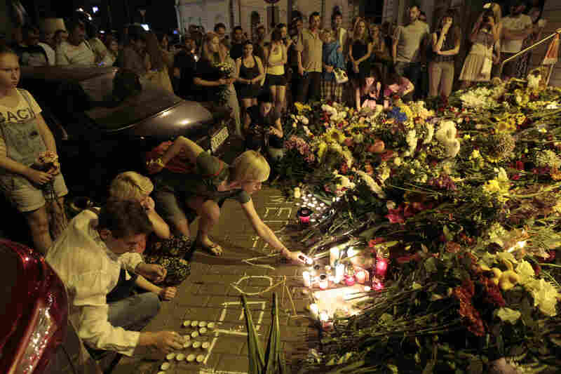 People hold candles and place flower tributes outside the Dutch Embassy in Kiev to commemorate victims of the crash.