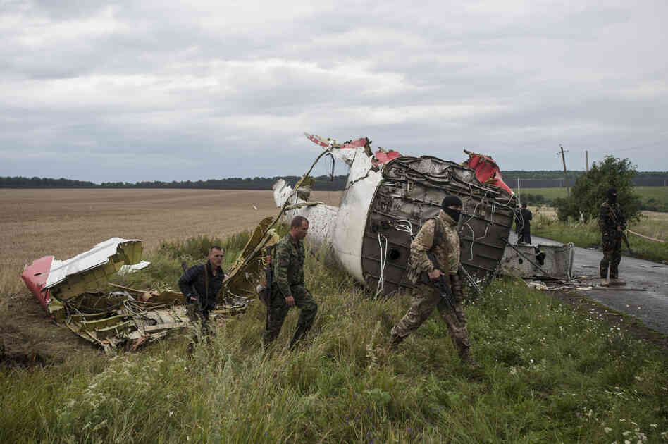 Pro-Russian fighters walk by the crash site near the village of Hrabove on Friday. Kiev officials accuse pro-Russian separatists of firing a missile at the jet, which crashed in territory held by rebel insurgents. The separatists, Ukraine's military and Russia have all denied any involvement in shooting down the plane.
