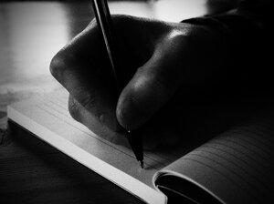 A hand drags a pen across a notebook.