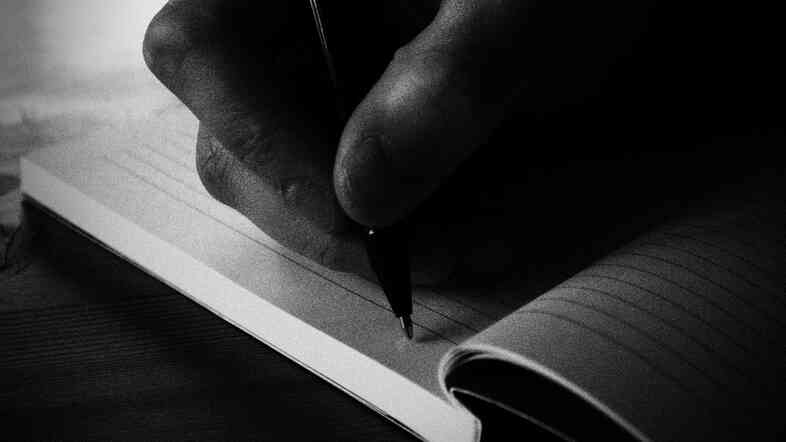 A hand drags a pen across a notebook.