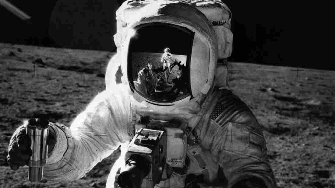 """During the Apollo 12 mission, astronaut Alan Bean holds a container of lunar soil. The astronaut Charles """"Pete"""" Conrad, who took the photograph, is reflected in Bean's faceshield. Bean says he used to think that in his lifetime, we'd build a base on the moon and start preparing to travel to Mars."""