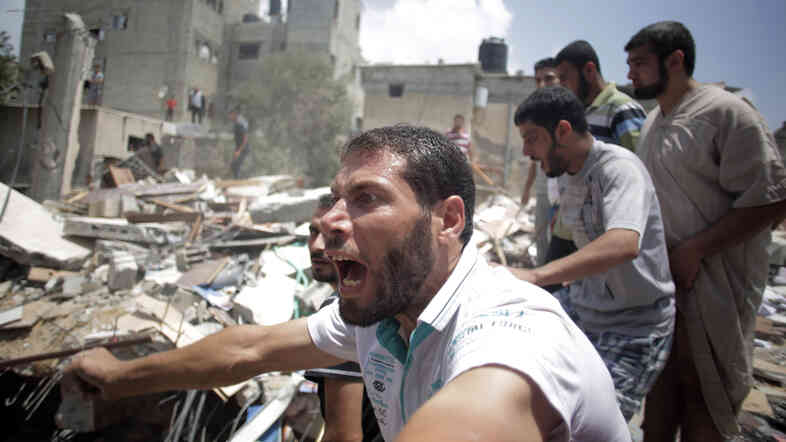 A Palestinian overcome by emotion watches rescuers carry a body from the rubble of a house which was destroyed by an Israeli missile strike, in Gaza City, on Monday.
