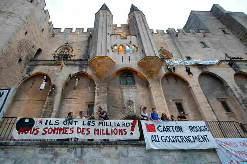 "Protest banners outside Avignon's Palais des Papes read: ""They have billions, we are millions"" (left) and ""Red card to the government."" Festival actors and technicians have been striking over talk of changes to their off-season unemployment benefits."
