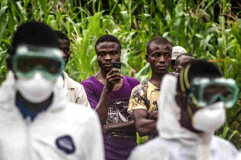 Villagers watch a Red Cross burial team carry out a neighbor who may have died of Ebola in the village of Pendembu, Sierra Leone. The goal is to prevent transmission of the virus from the body of the deceased.