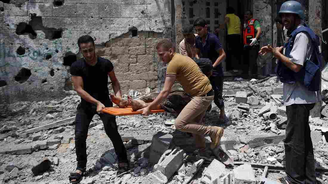 Palestinian medics remove a body from Gaza City's Shejaiya neighborhood on Sunday. The area was the scene of the heaviest fighting since the Israeli ground incursion began in Gaza last Thursday.