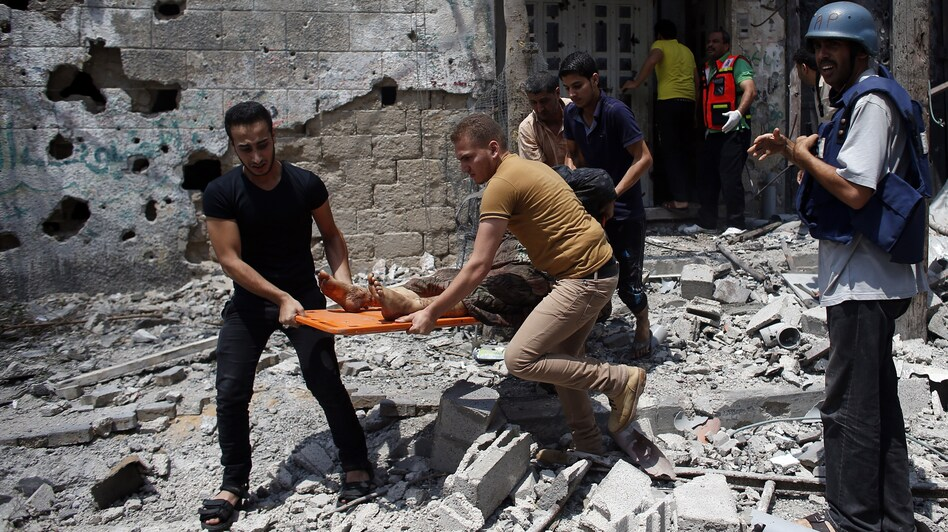 Palestinian medics remove a body from Gaza City's Shejaiya neighborhood on Sunday. The area was the scene of the heaviest fighting since the Israeli ground incursion began in Gaza last Thursday.
