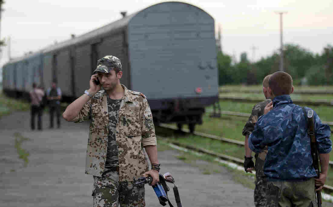 A pro-Russian rebel talks on a phone as a refrigerated train loaded with the bodies of victims from Flight MH17 leaves the station in Torez, east