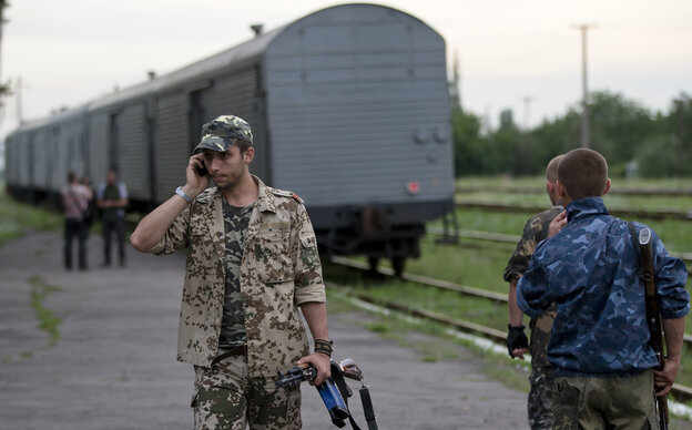 A pro-Russian rebel talks on a phone as a refrigerated train loaded with the bodies of victims from Flight MH17 leaves the station in Torez, eastern Ukraine, about 9 miles from the crash site of the Malaysia Airlines jetliner.