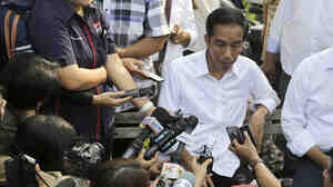 Indonesian presidential candidate Joko Widodo talks to the media during his visit at a reservoir development project in Jakarta, Indonesia, on Tuesday.
