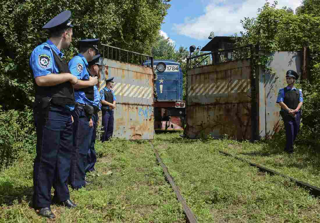 Police officers secure a refrigerated train loaded with bodies of the passengers of Malaysian Airlines flight MH17 as it arrives in a Kharkiv factory on Tuesday.