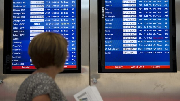 A woman passes by a departure board at Philadelphia International Airport showing that US Airways Flight 796 to Tel Aviv has been canceled Tuesday. (AP)