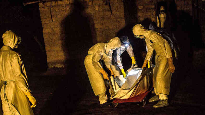 Eerie protective suits and shiny body bags have fueled rumors about the origins of Ebola. In this photo, a burial team removes the body of a person suspected to have died from the virus in the village of Pendembu, Sierra Leone.