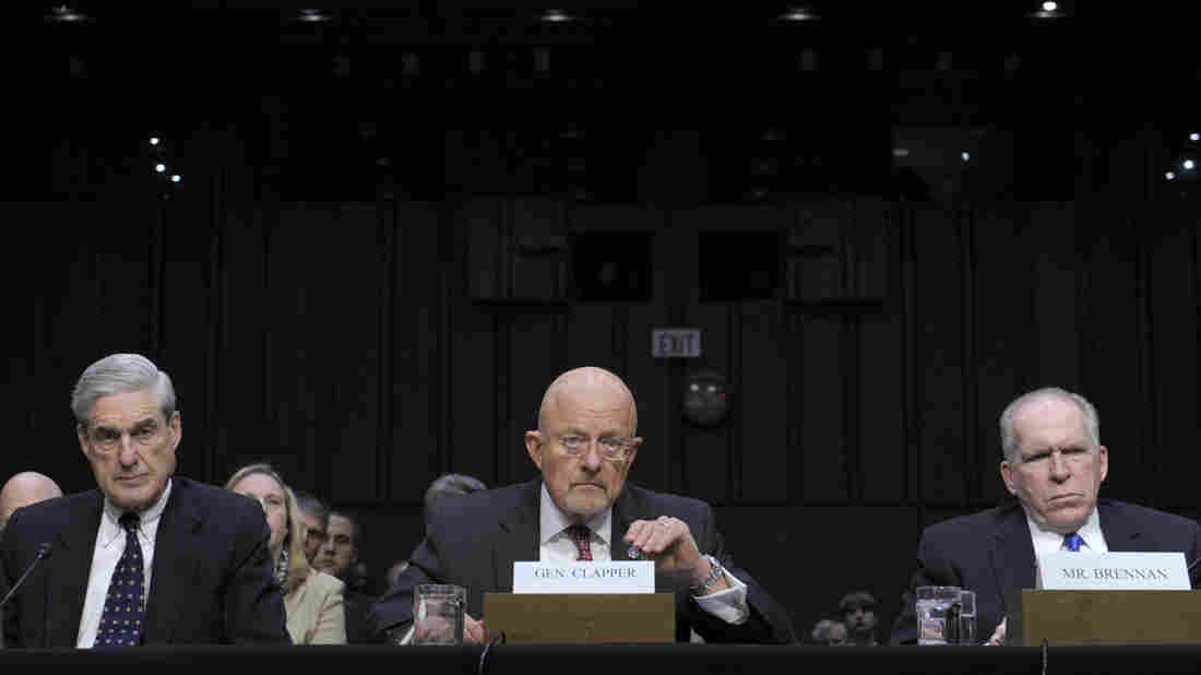 "Director of National Intelligence James Clapper (center), accompanied by FBI Director Robert Mueller (left) and CIA Director John Brennan, testifies on Capitol Hill on March 12, 2013. When questioned, Clapper said the NSA did not collect data on Americans. He later acknowledged his response was ""clearly erroneous."""