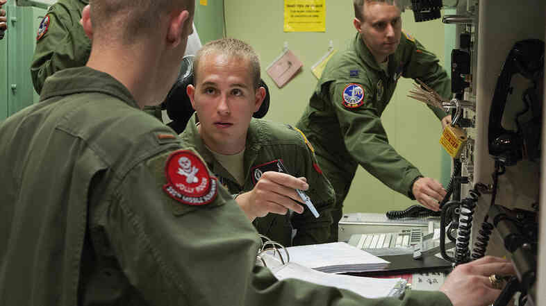 First Lt. Patrick Romanofski (center) and 2nd Lt. Andrew Beckner (right) practice the launch of nuclear weapons. Promotions are now more strongly influenced by hands-on performance in this simulator.
