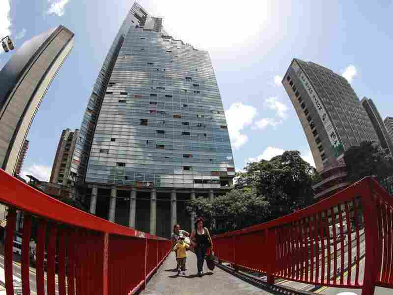 Squatters living at the Tower of David, an abandoned, unfinished skyscraper in Caracas, began to be evicted and relocated Tuesday.